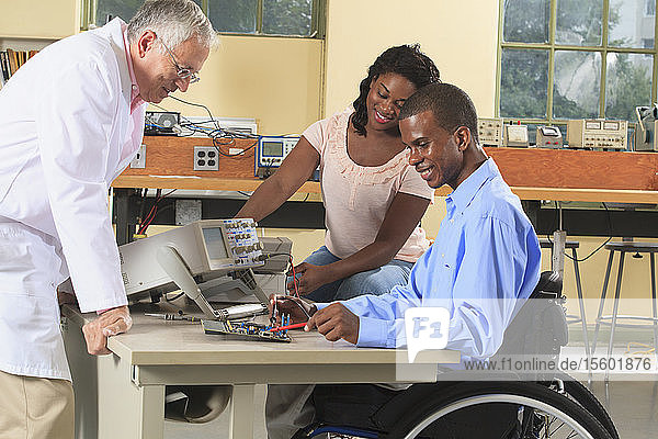 Professor and engineering students in an electronics classroom  working with a multimeter