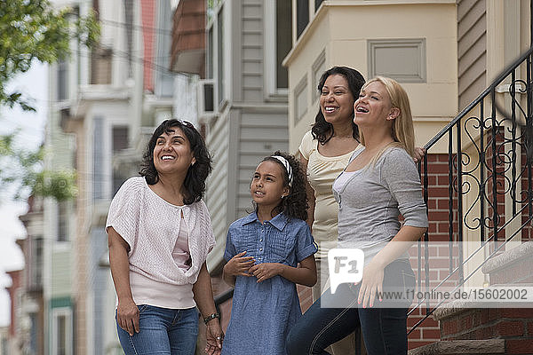 Two Hispanic women standing with their daughters