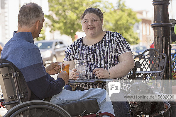 Woman with Visual Impairment sitting at a cafe with her father and service dog