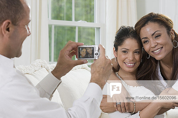 Hispanic man taking a picture of two Hispanic women with a digital camera