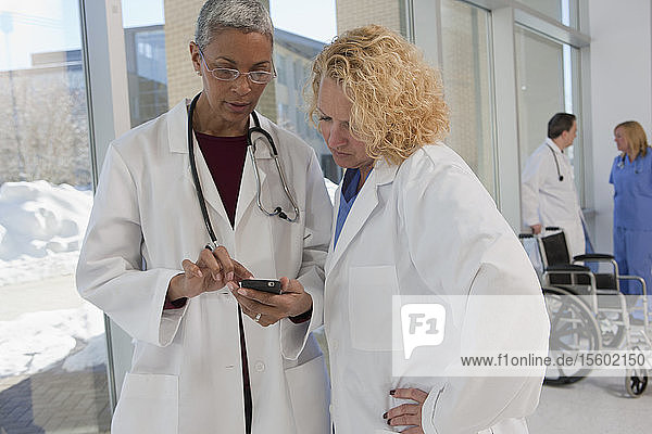 Two female doctors reading text message on a mobile phone with their colleagues standing in the background