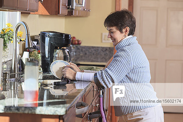Woman with Cerebral Palsy using crutches and washing dishes in her kitchen