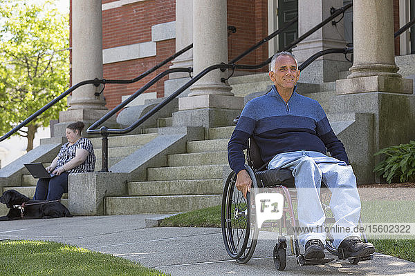 Man with Spinal Cord Injury sitting in wheelchair with his daughter in background who is Blind