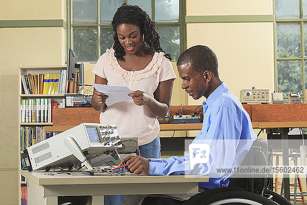 Engineering students in an electronics classroom  one in a wheelchair working with a multimeter