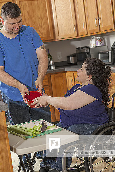 Woman with Spina Bifida and her husband preparing dinner in their kitchen