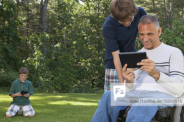 Man with spinal cord injury in wheelchair with his sons reading a tablet