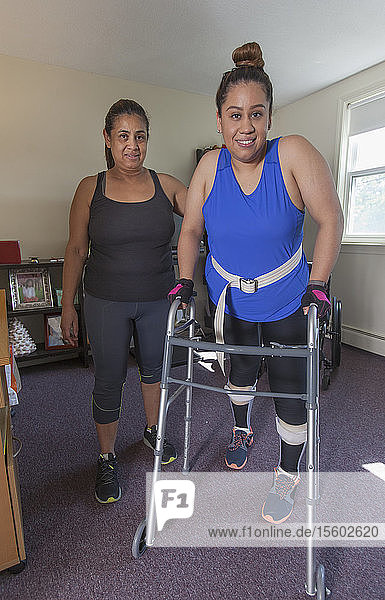 Woman with spinal cord injury getting up into her walker