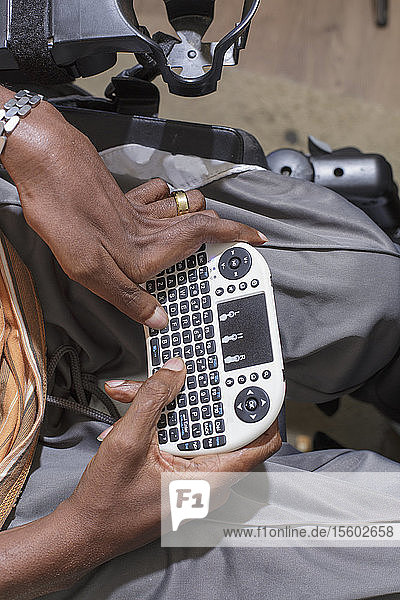 Man with Guillain-Barre Syndrome using his Bluetooth mini keyboard in his power chair