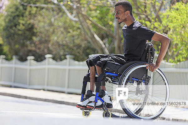 Man in a wheelchair who had Spinal Meningitis crossing the street