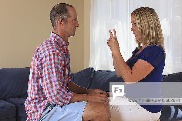 Husband and wife with hearing impairments signing in American sign language