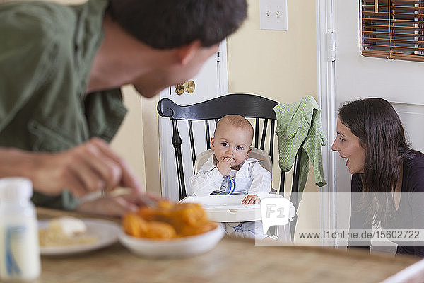 Father preparing baby's meal and mother watching