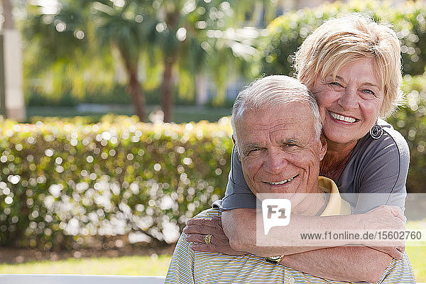 Portrait of a senior woman hugging a senior man from behind