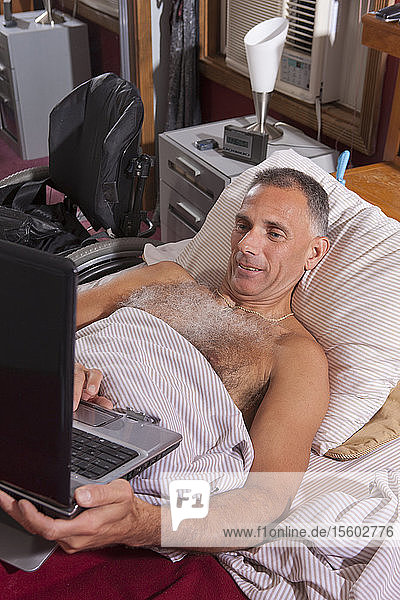 Man with spinal cord injury in the bed using his laptop
