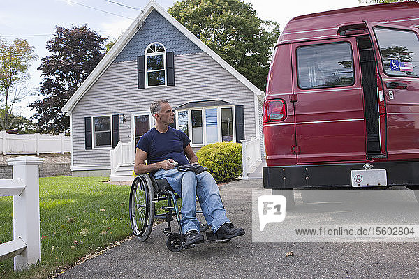 Man with spinal cord injury in a wheelchair getting in his accessible van with a remote