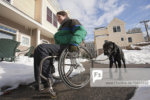 Woman with multiple sclerosis in a wheelchair with a service dog in winter