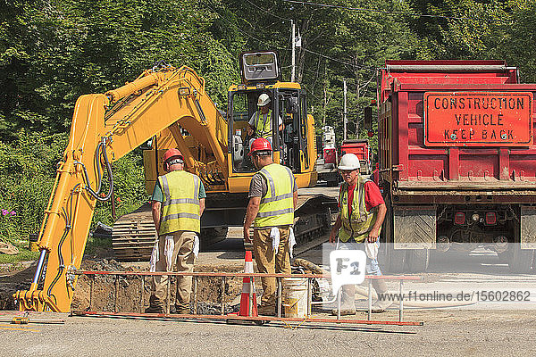 Construction workers watching excavators digging hole on watermain project
