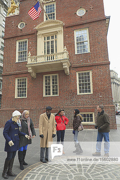 Tourists in front of The Old State House and looking at The Boston Massacre Historic Site  Boston  Suffolk County  Massachusetts  USA Tourists in front of The Old State House and looking at The Boston Massacre Historic Site, Boston, Suffolk County, Massachusetts, USA