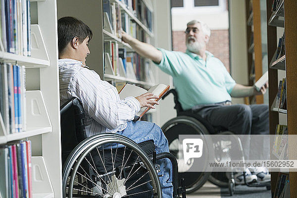 Middle-aged man with Muscular Dystrophy picking a book from a bookshelf with a young woman reading a book in a library