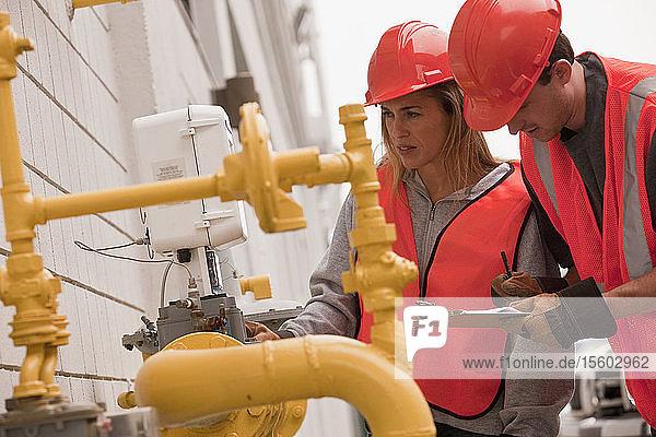 Process engineers taking meter reading near pipeline