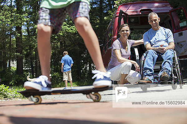 Couple watching their son on skate board