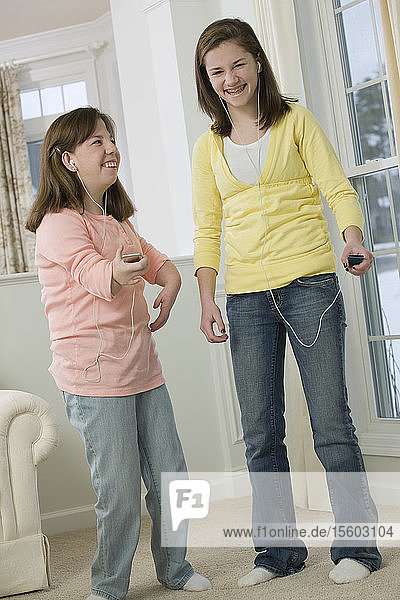 Two teenage girls listening to MP3 players  one with birth defect