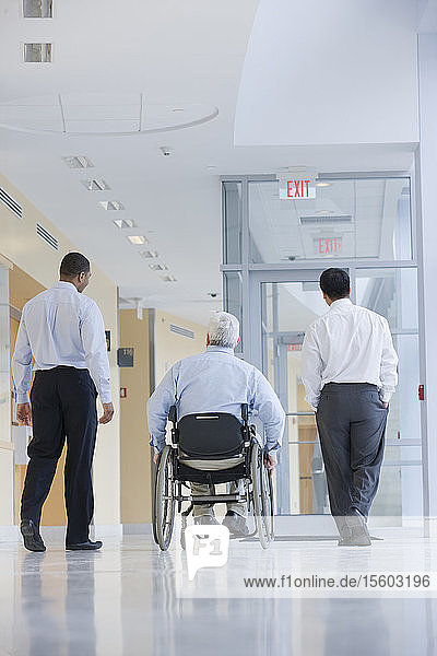Rear view of three professors in a corridor  one with Muscular Dystrophy