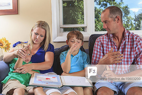 Family with hearing impairments looking at a photo album and signing 'flag' in American sign language on their couch