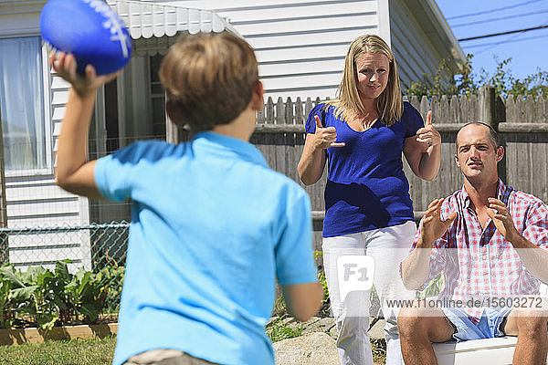 Family with hearing impairments playing football and signing 'play and pass' in American sign language in backyard