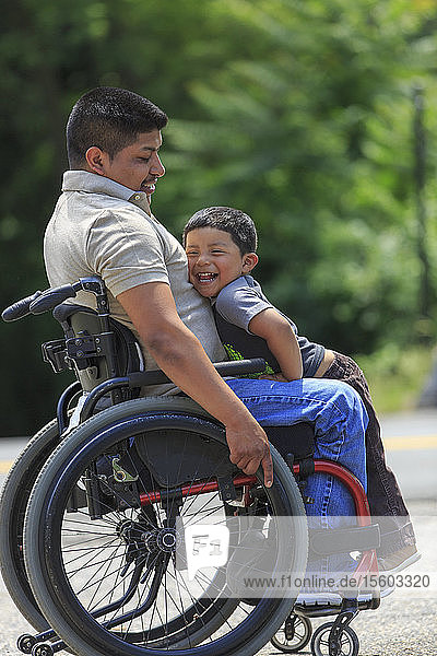 Happy Hispanic man with Spinal Cord Injury in wheelchair with his son
