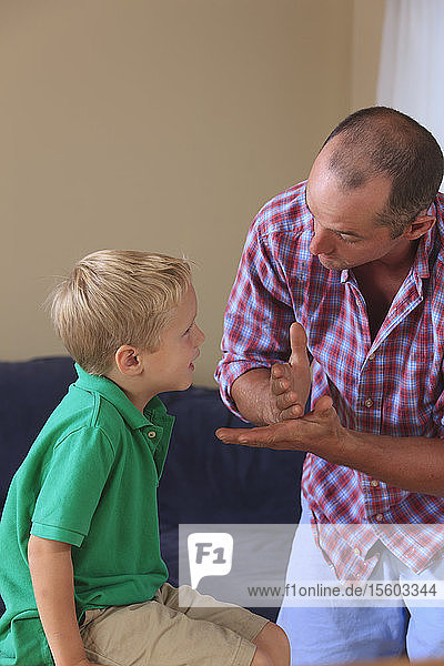 Father and son with hearing impairments signing 'stop' in American sign language