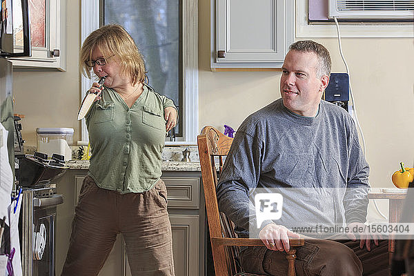 Woman with TAR Syndrome picking up a knife with her husband in the kitchen