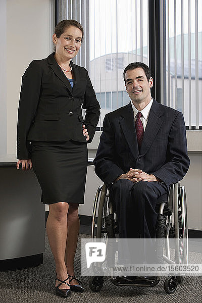 Portrait of a businesswoman standing beside a Businessman with spinal cord injury