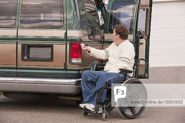 Man with spinal cord injury using magnetized remote to close his accessible vehicle