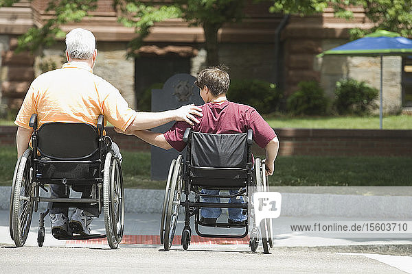 Rear view of a middle-aged man and a middle-aged woman with Muscular Dystrophy crossing a road in wheelchairs