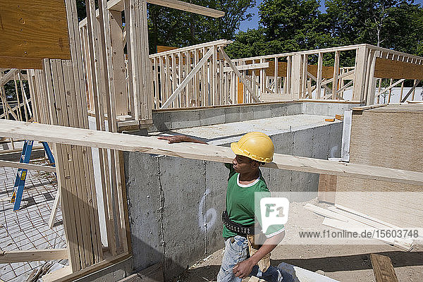 Carpenter carrying a plank at a construction site