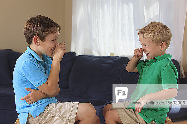 Boys with hearing impairments signing 'bird' in American sign language on their couch