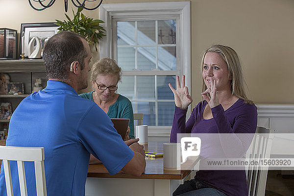 Three people having a meeting and two communicating in ASL about 'Perfect' at home