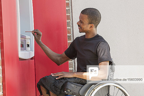 Man in a wheelchair who had Spinal Meningitis using a bank ATM