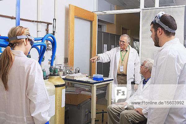 Professoren im Gespräch mit Ingenieurstudenten über ein Wasserreinigungssystem für ein Chemielabor