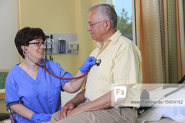 Nurse with Cerebral Palsy checking a patient's heart in a clinic