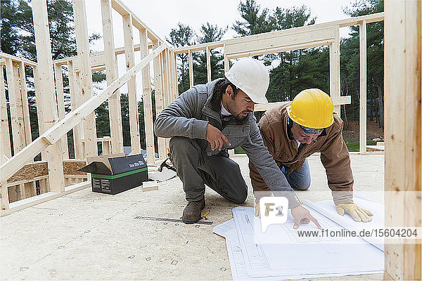 Construction supervisor reviewing home design plan with a carpenter