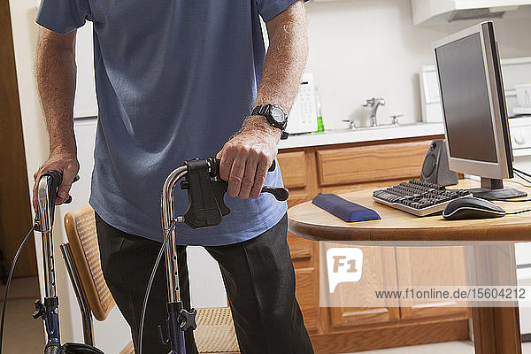 Man with Ataxia holding his walker with his computer in kitchen