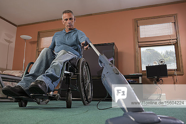 Man with spinal cord injury in a wheelchair using a vacuum cleaner at home