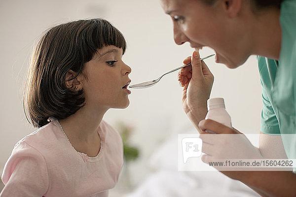 Nurse giving young girl medicine with spoon