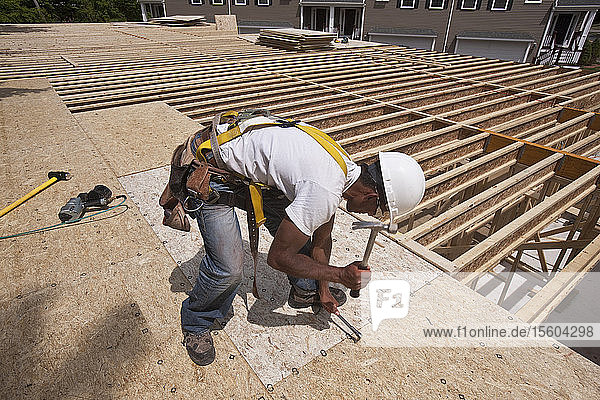 Carpenter hammering particle board in place