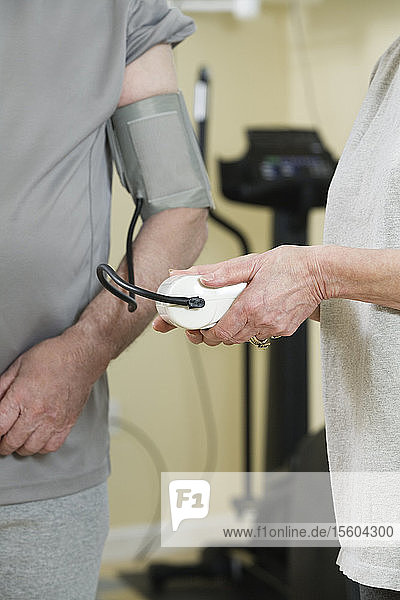 Woman checking blood pressure of man in the gym.