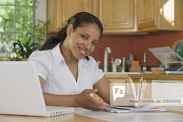 Hispanic woman sitting in front of a laptop and holding bills in the kitchen