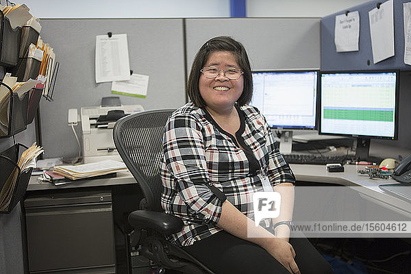 Portrait of happy Asian woman with a Learning Disability smiling in office