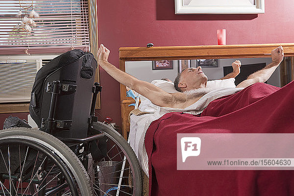 Man with spinal cord injury stretching on the bed