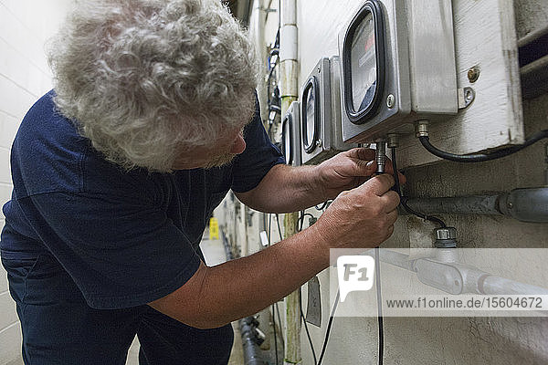 Engineer connecting O2 electrochemical sensor probe cable to meter in water treatment plant